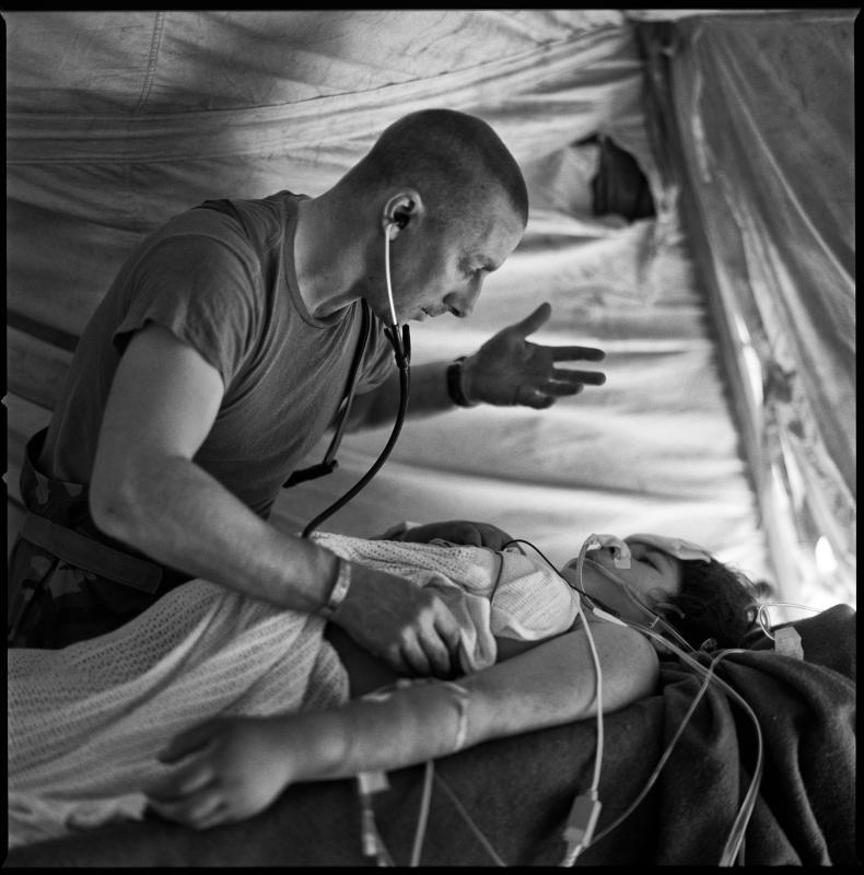Captain Moore recovers a pregnant Iraqi Shia woman from surgery.  She had been shot through the abdomen by Iraqi Sunni forces.  I did not see it at the time, but the light reflecting off the desert sand though the elevated sides of the tent created a presence, a power behind Captain Moore, guiding and working through him.  In my mind, the photograph captures four souls because, at this point at least, the baby was still viable. : Aid and Comfort to the Enemy : TIMOTHY FLOYD PHOTOGRAPHER, NATURE PHOTOGRAPHY, PHOTO ESSAYS, PHOTOJOURNALISM